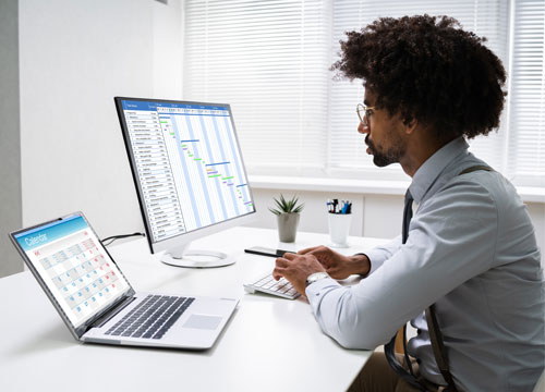 Person of Color / Büromanager koordiniert Liefertermine und Fristen in einem Gantt-Diagramm an einem Desktop-Rechner am Schreibtisch in einem hellen Büro